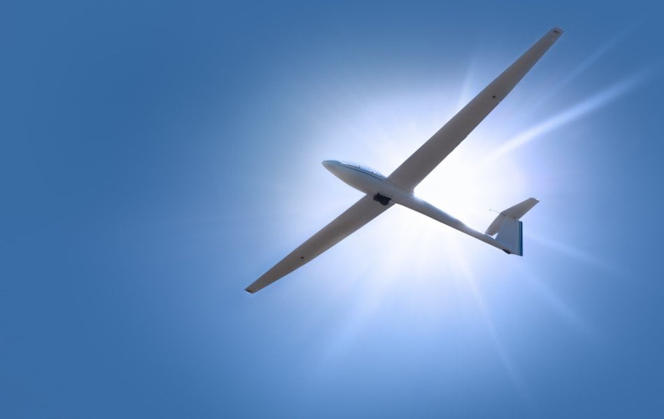 Svævefly på himlen med solen i baggrunden